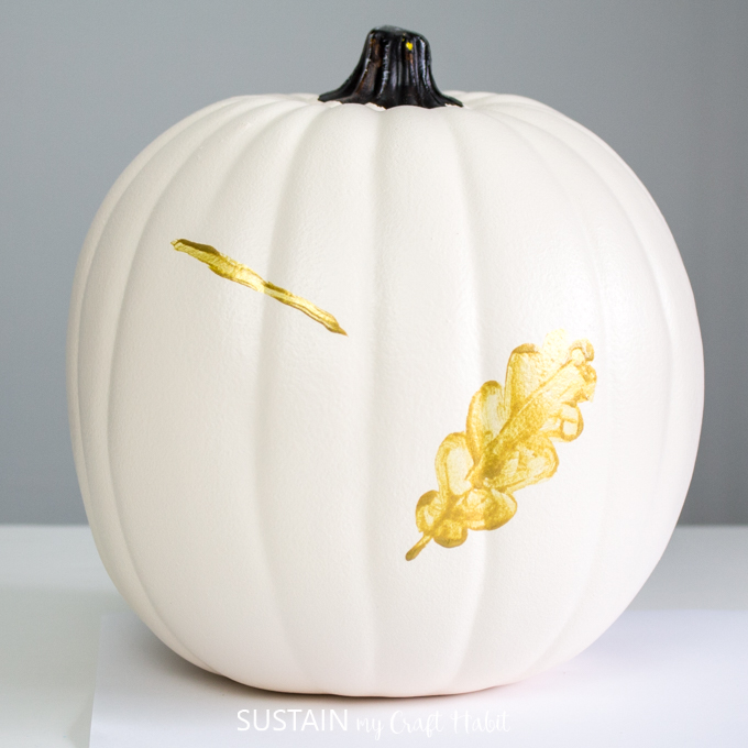 White pumpkin with one gold leaf painted on. Also, one angled horizontal line of gold paint on the front.