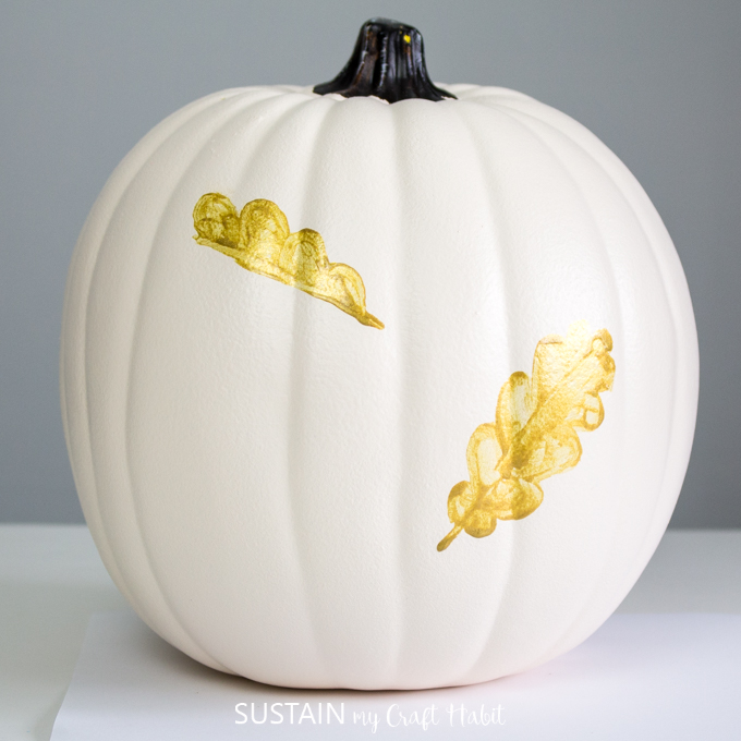 White pumpkin with one gold leaf painted on. Half of a gold leaf has been painted as well.