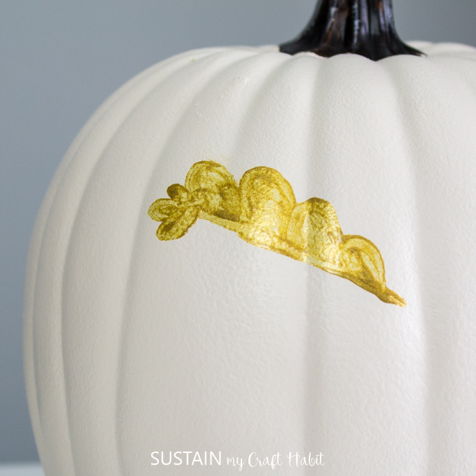 close up of white pumpkin and half painted gold leaf.