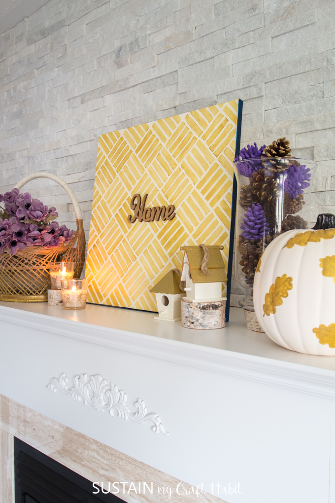 """Decorations placed on a white fireplace mantle. There is a basket with purple flowers, candles, a gold canvas sign with the words """"home"""" on it, wooden bird houses, vase with purple pine cones and a gold leaf painted pumpkin"""