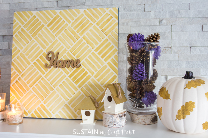"""Close up of decorations. There are candles, a gold canvas sign with the words """"home"""" on it, wooden bird houses, vase with purple pine cones and a gold leaf painted pumpkin."""