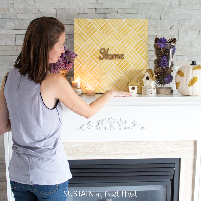 Woman placing autumn decorating elements onto a fireplace mantle.