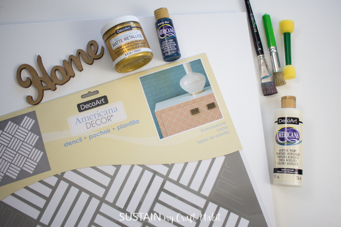 """materials needed for craft project. wooden cut out of the word """"home"""". gold metallic paint and white paint. paint brushes, stencil brush and stencil."""