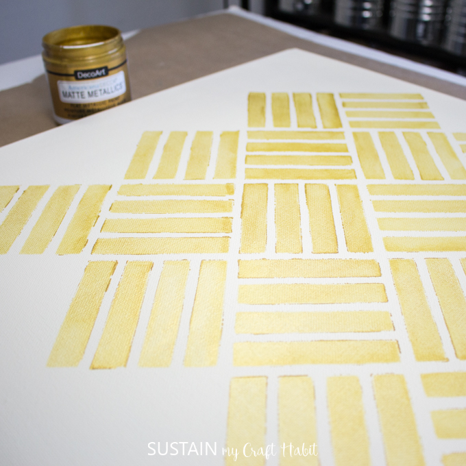 progress of the painted canvas with stencilled design using the gold paint.