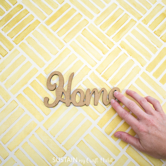 """woman glueing wooden cut out of the word """"home"""" onto completed stencilled canvas"""