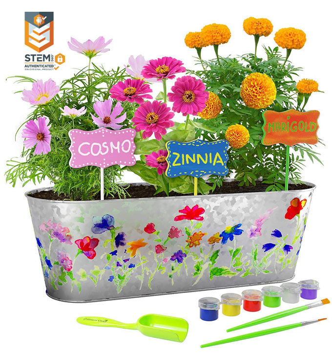 A painted silver planter filled with flowers and name markers. Also shows a shovel, 2 paint brushes and paints.