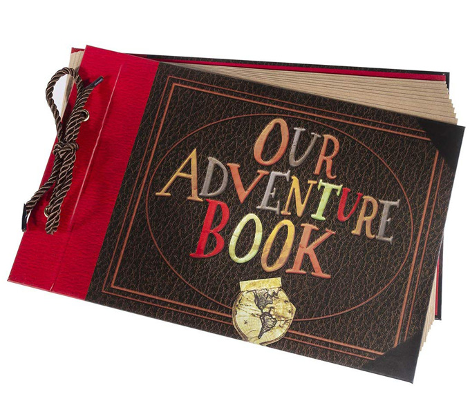 "A brown and red book bound with brown string and the words ""our adventure book"" written on the front."