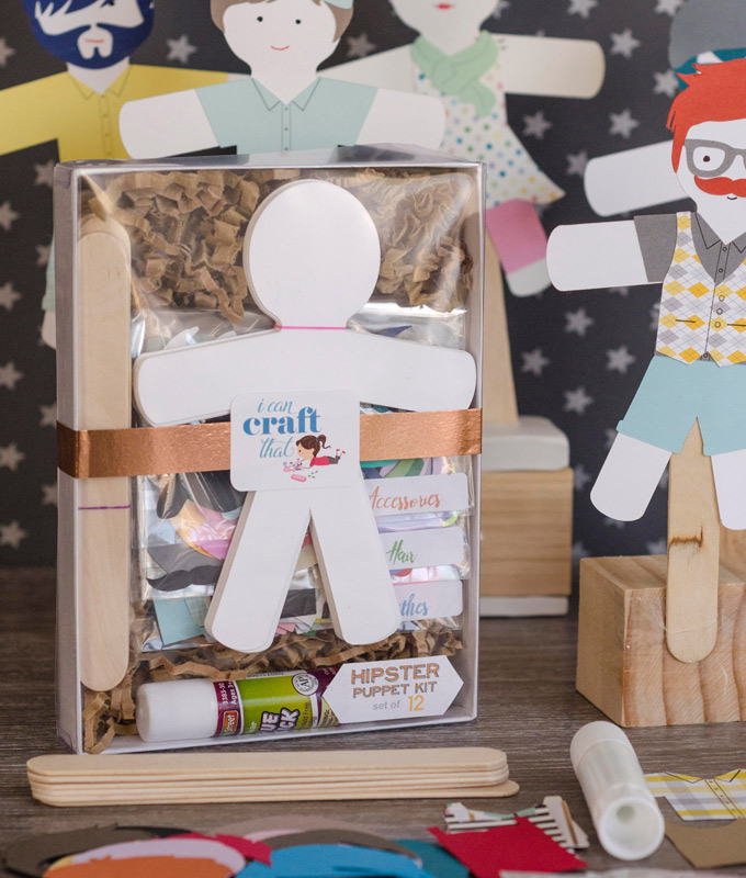 Paper dolls, glue, wooden sticks, and paper accessories wrapped in a box placed beside finished paper dolls on wood stands.