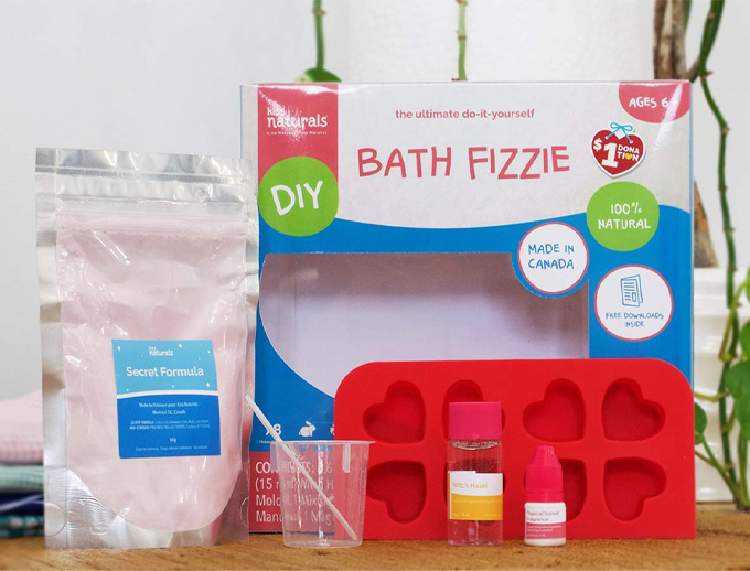 "Ingredients needed to make a bath bomb. The kit includes a bag with the words ""secret formula"", a red silicon mold, cup and stir stick and oils."