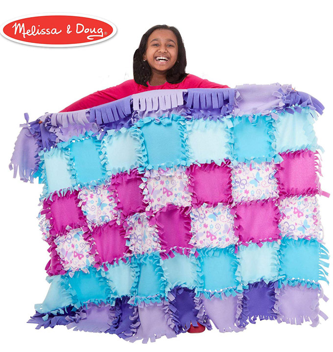 Girl showing a completed fleece quilt.