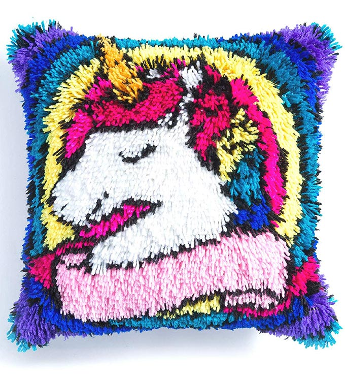 A square pillow made with yarn and with a unicorn image on the front.