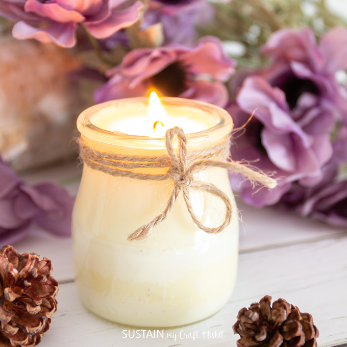 Close up image of lit DIY fall candle. A piece of twine is tied around the neck of the glass jar. Purple flowers are gently blurred in the background.