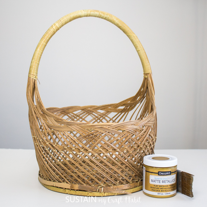 A wicker basket, Matte Metallics Gold paint and a paintbrush.