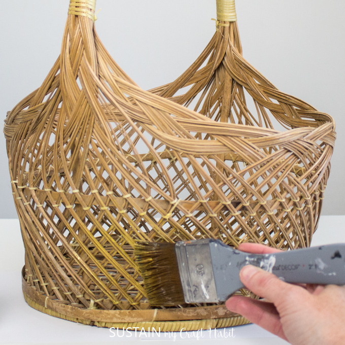 A hand painting the bottom of wicker basket with gold paint.