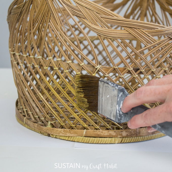 Close up of hand painting wicker basket with gold paint.