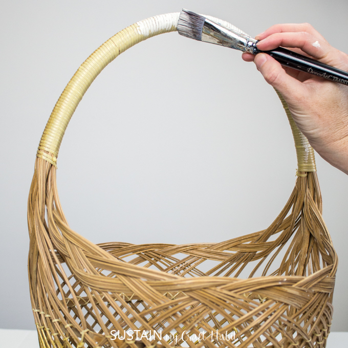 "Hand painting handle of the wicker basket in ""Buttermilk"" color."