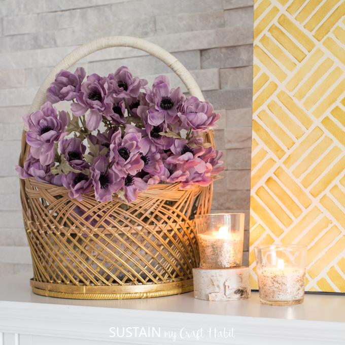 Gold painted wicker basket with purple flowers beside 2 lit candles.