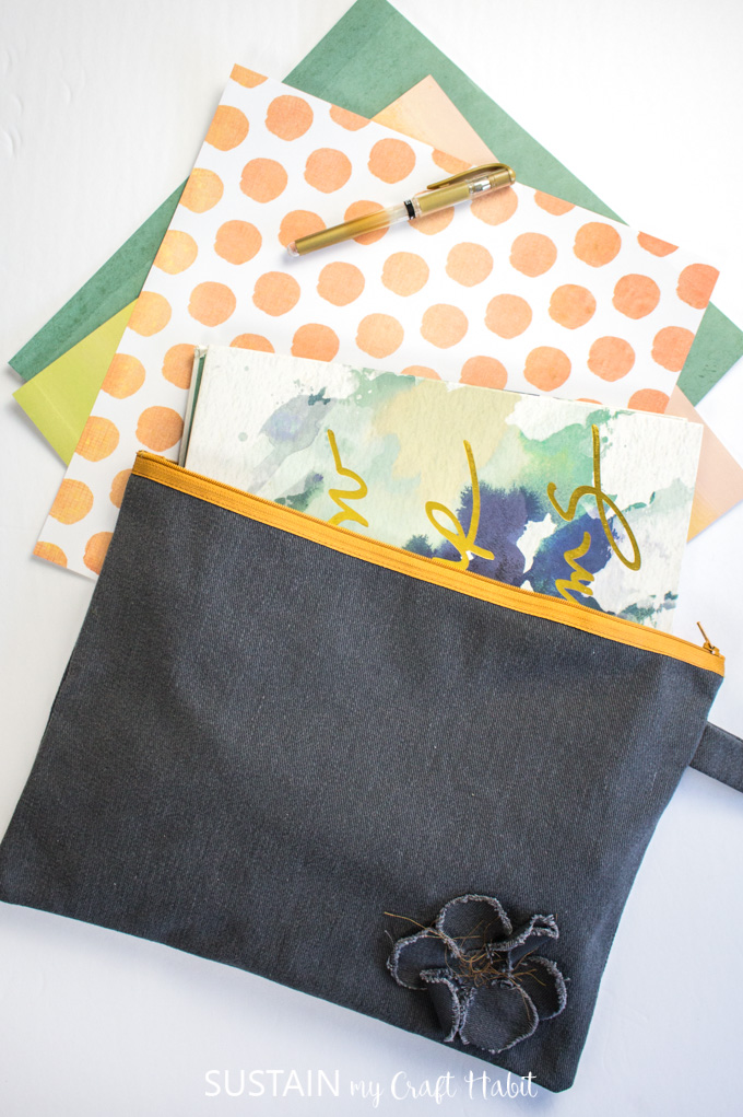 A notebook and decorative paper spilling out of the finished oversized pencil case made from this how to sew a pencil case with a zipper tutorial.