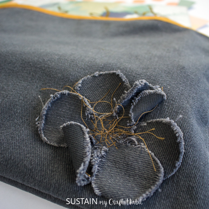 Close up view of the simple flower embellishment on a large zippered pencil case.