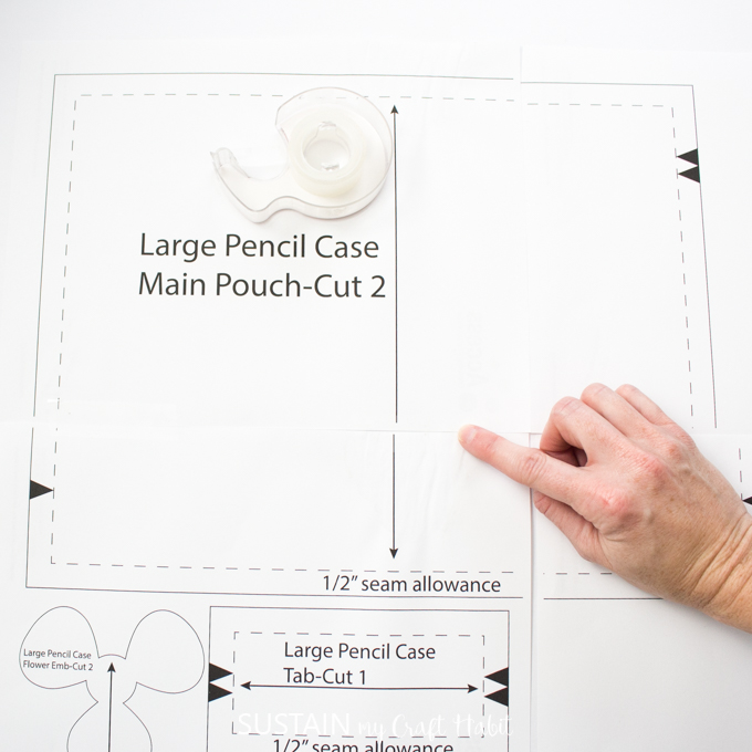 Demonstrating how to assemble the pieces of the large DIY pencil case pattern printout.