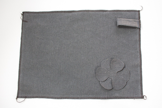 Placement of the flower embellishment on the handmade pencil case.