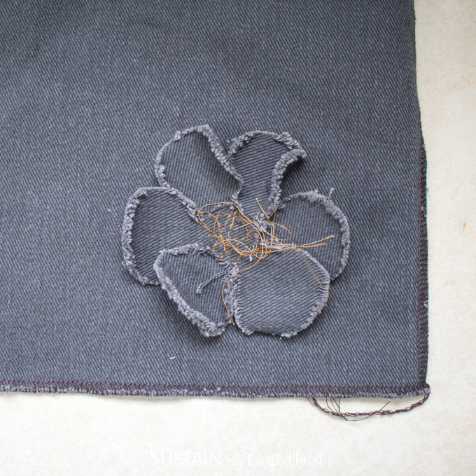 Close up image showing the frayed edges of the handmade flower embellishment.