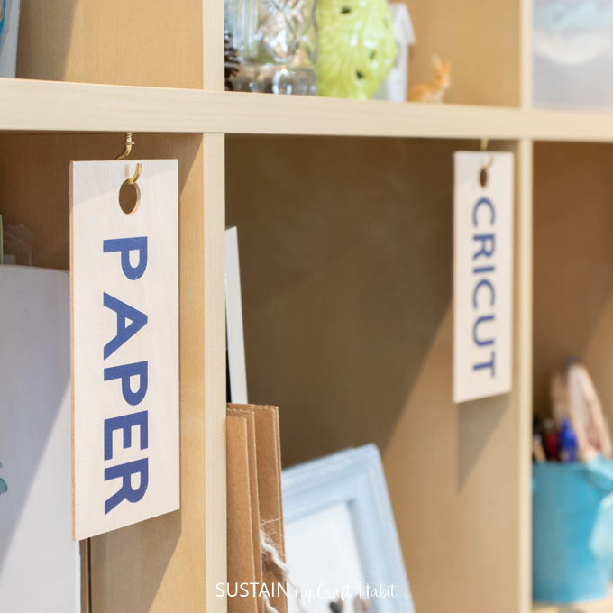 Wooden organization labels hanging in cubby's to identify craft supplies in a craft room.