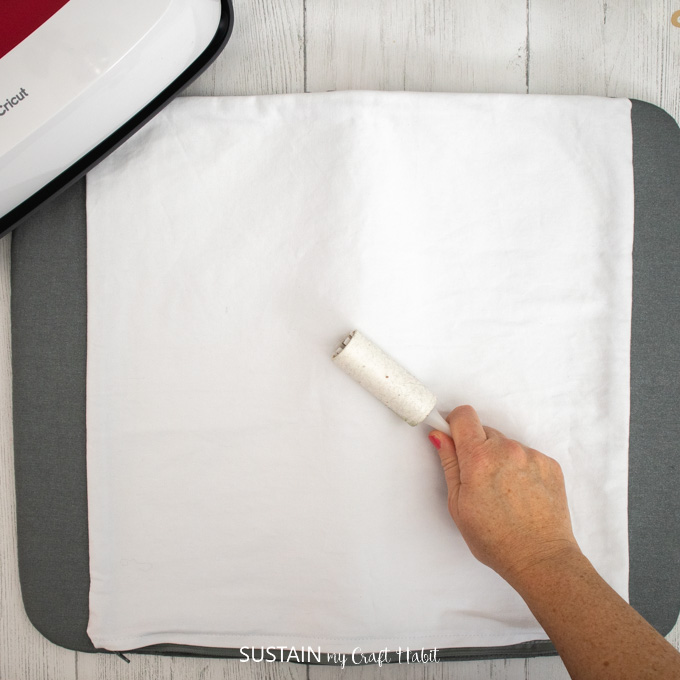 Using a small lint roller to remove lint from pillow cover before applying the adhesive vinyl.