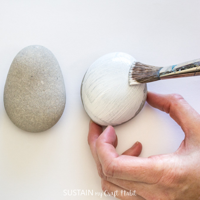 Painting one rock with white paint.