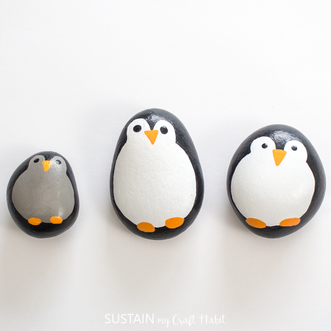 Three completed penguin rocks on a white surface.