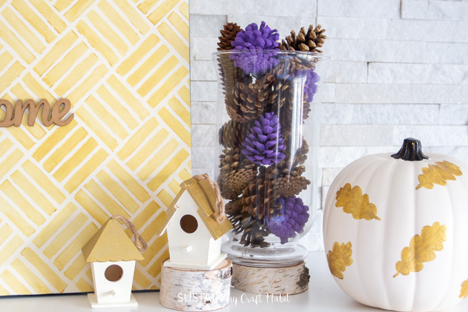 A tall glass vase filled with natural, gold and lavender painted pinecones.