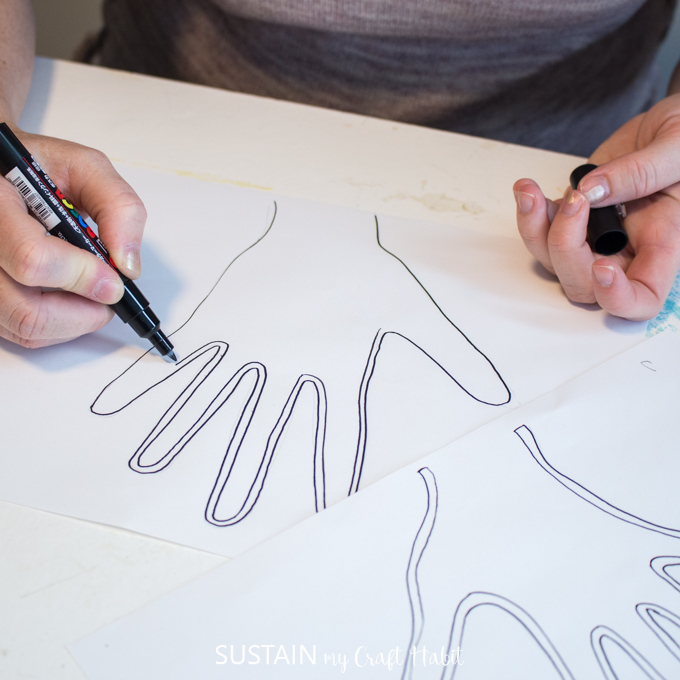 Woman tracing the outline of her child's hand with a black marker.