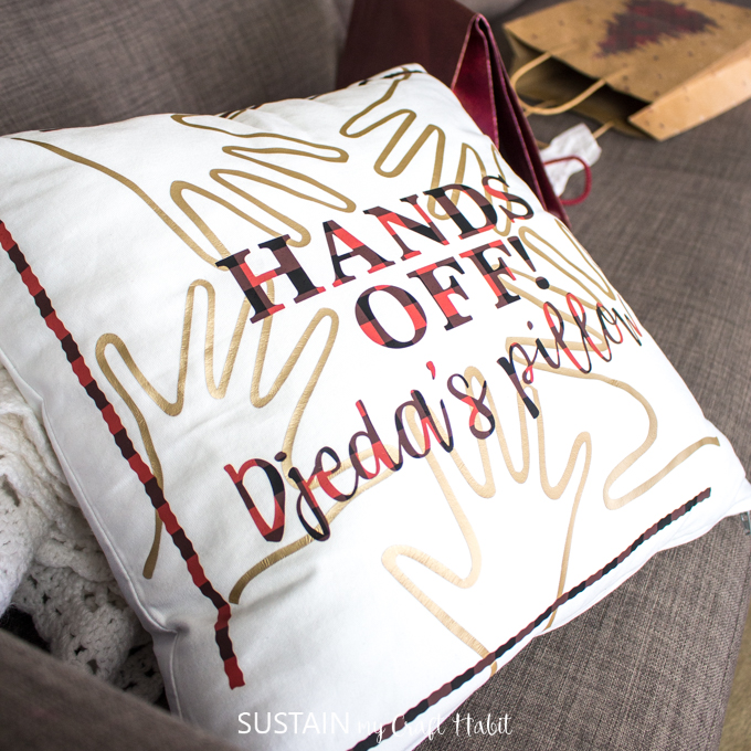 """Close up view of """"Hands off! Djeda's pillow"""" on a couch surrounded by opening gift bags."""