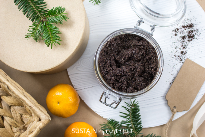 The glass container filled with the coffee sugar scrub on a white wood surface surrounded by mandarin oranges and evergreen tree clippings.