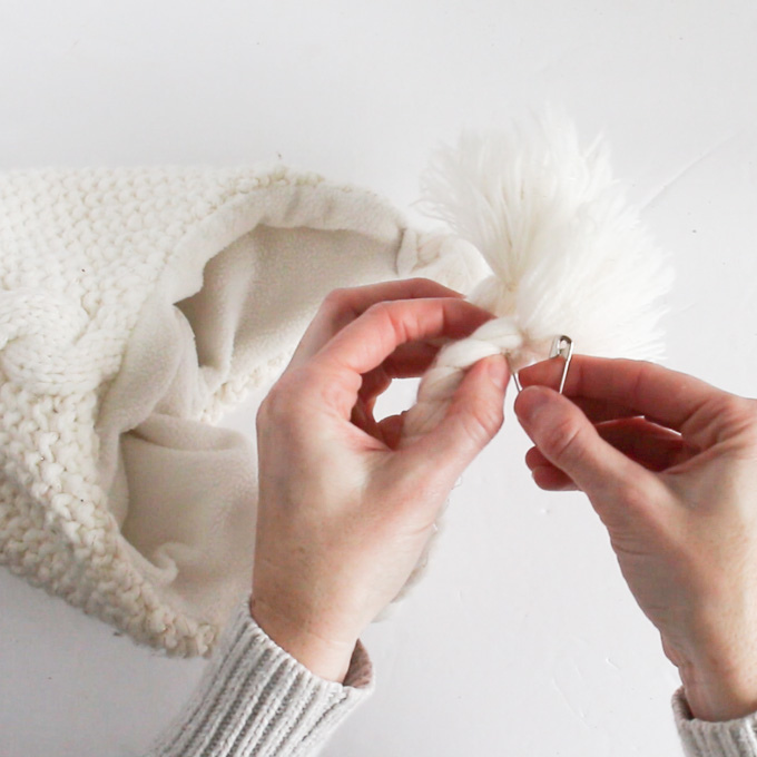 attaching a safety pin to the bottom of the white winter hat.