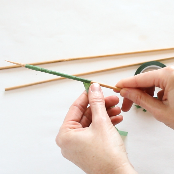Covering the bamboo skewer with green floral tape