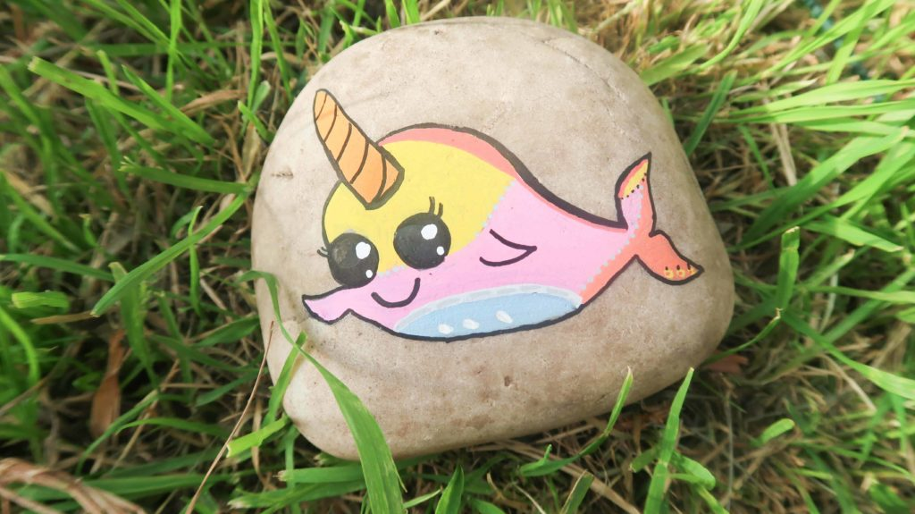 Rainbow narwhal painted on a rock and placed in the grass.