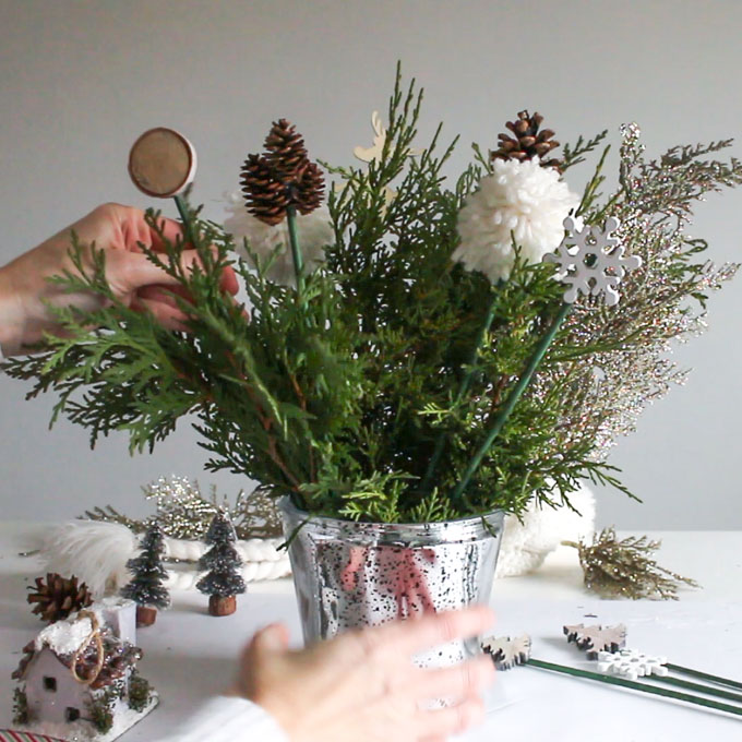 Filling silver container with fresh greenery and decorative picks.
