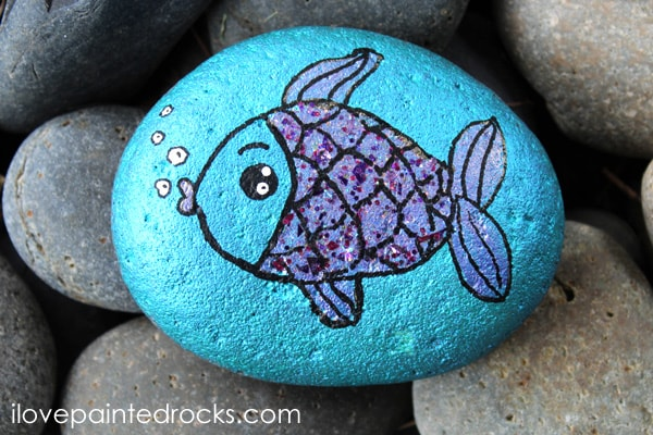 A rock painted in irridescent blue with a purple fish overlay