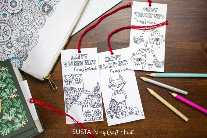 A set of three woodland themed coloring bookmarks made with the Cricut maker. The bookmarks are laid out on a dark wood surface surrounded by pencil crayons.