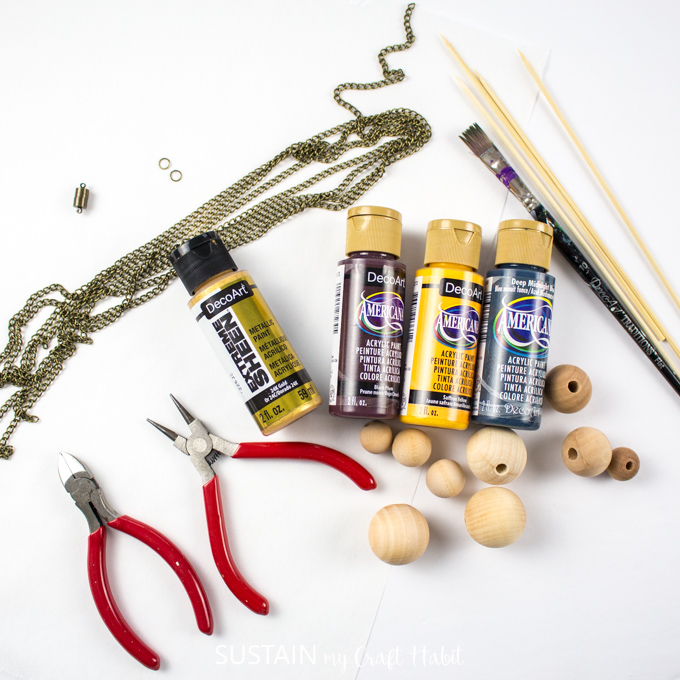 Materials needed for the jewelry project, including wood beads, gold jewelry chain, gold clasps,wooden skewers, paint, paint brushes and wire cutters.