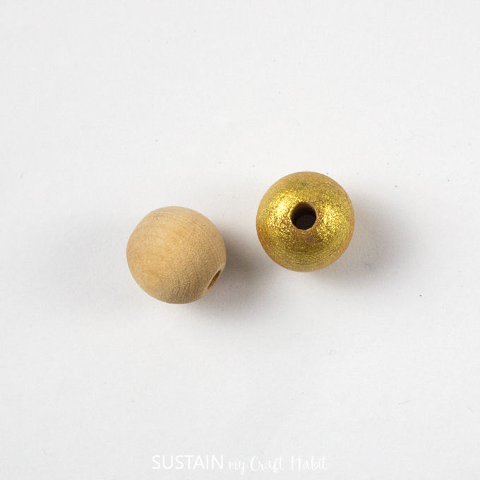 Two wooden beads with one wood bead painted gold.