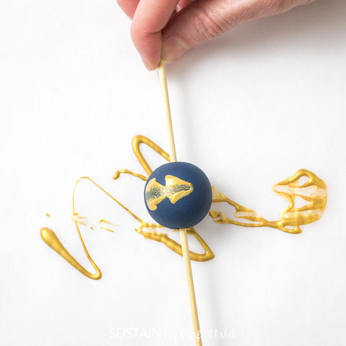 Rolling blue painted wood bead in gold paint