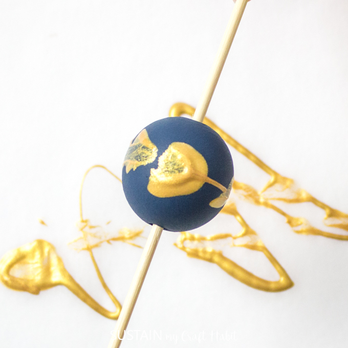 Close up of blue painted wood bead with gold splatter