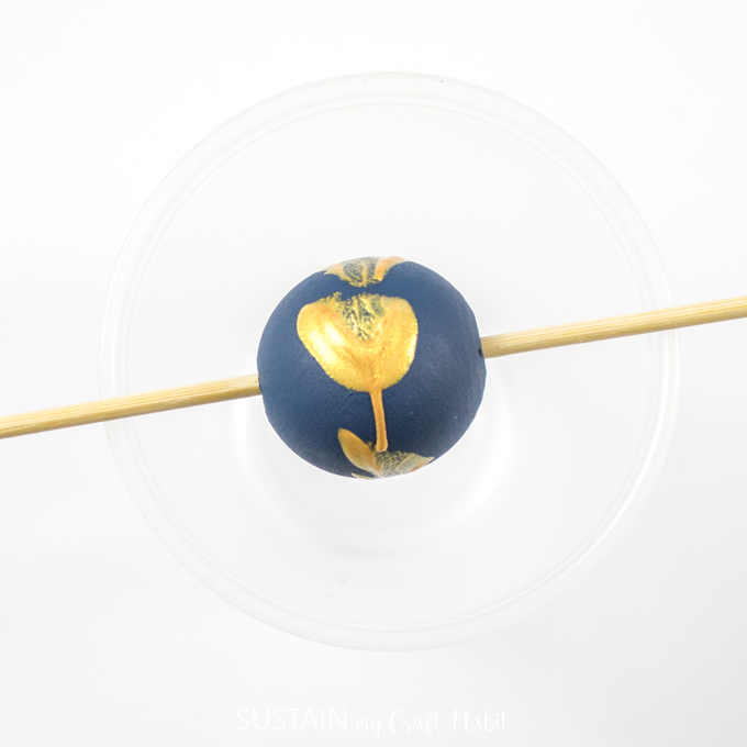 Blue painted wood bead with gold splatter placed on wooden skewer.