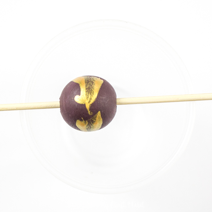 Purple painted wood bead with gold splatter placed on a wooden skewer.