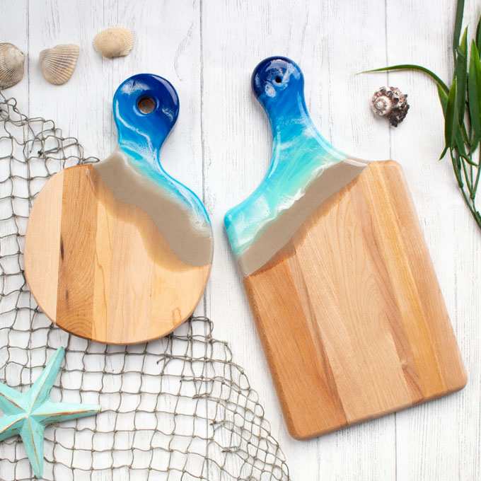 Two wooden cutting boards with resin handles resembling the seashore.