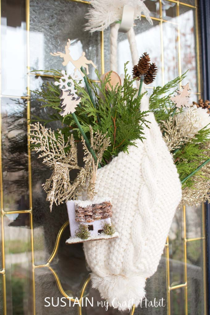 A white winter hat hanging from a glass door. The hat is filled with greenery and small decorative picks such as a snowflakes, trees, pine cones, wood slices and a birdhouse.