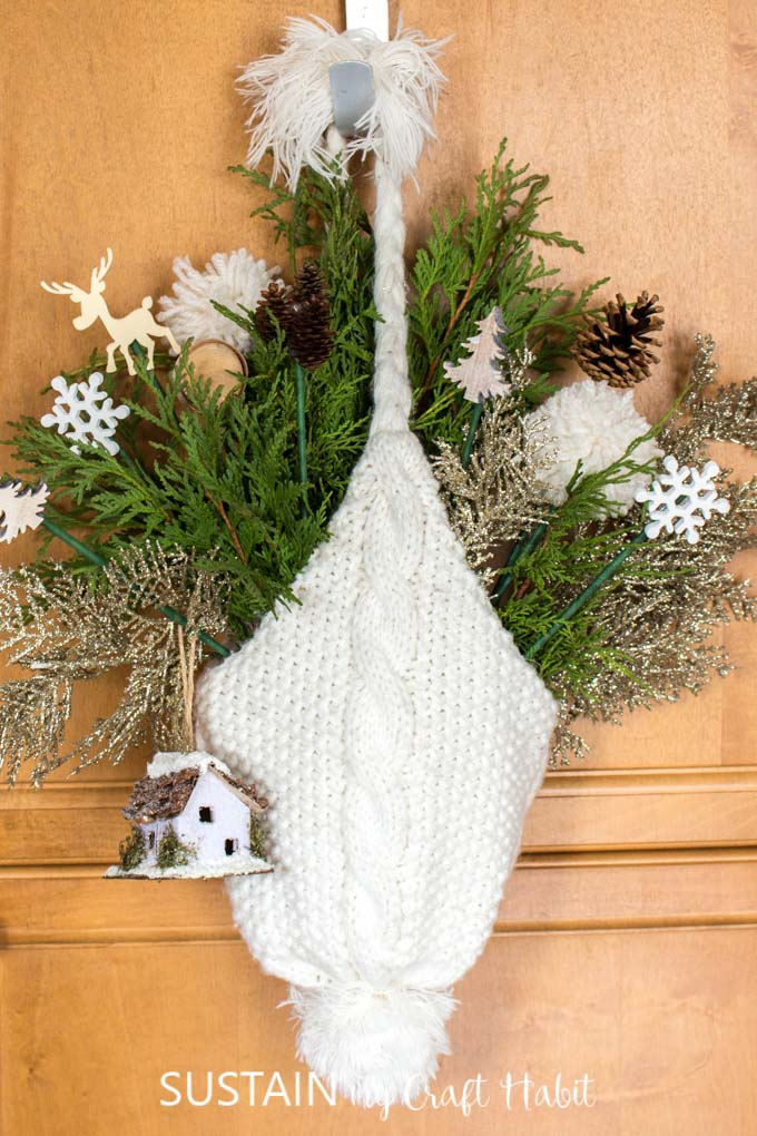A white winter hat hanging from a hook. The hat is filled with greenery and small decorative picks such as a snowflakes, trees, pine cones, wood slices and a birdhouse.