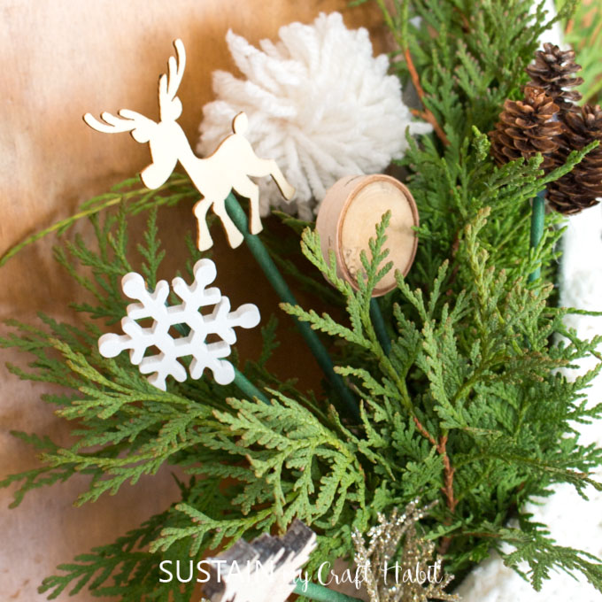 A close up of greenery mixed with decorative picks such as a snowflake, a reindeer,wood slice, a pom pom and pine cones.